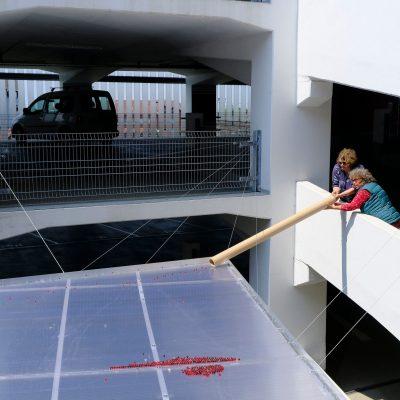 Lisa Premke befüllt mit Hilfe ihrer Mutter das Klangkunstobjekt LACHE im Parkhaus Lehrte mit 8.000 Glasmurmeln.